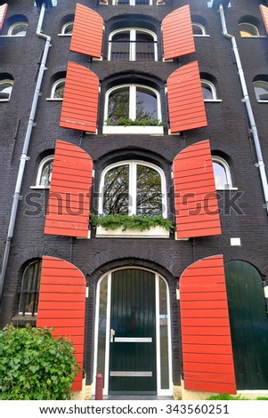Red open shutters on black painted facade of traditional building in Amsterdam, Holland  - stock photo