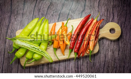 Red orange and green chili Peppers over wooden background ,Banana Pepper, Paprika, Garden Pepper, Chili Plant, Red Pepper, Spanish pepper, Sweet Pepper - stock photo