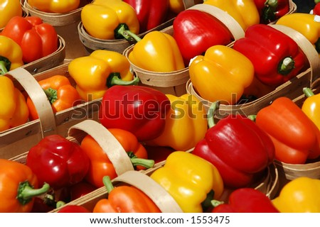 Red, orange and yellow bell peppers in farmer baskets