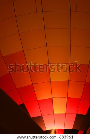 Red Orange And Yellow Checkered Hot Air Balloon With Burners on at Night - stock photo