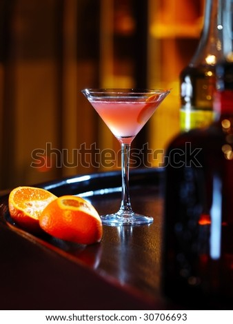 red orange cocktail with orange near the bottle on the wooden bar - stock photo