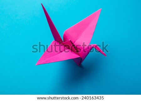 red origami paper on a blue background - stock photo