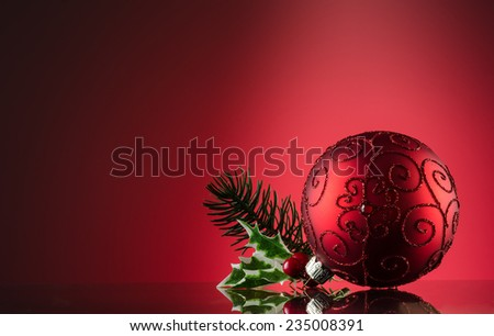 Red ornament with pine on a reflective surface. Red Background and copy space - stock photo