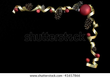 Red ornaments and gold ribbon on black background framing space for text