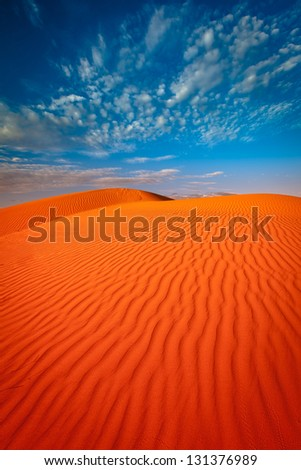 Red outback ripple sand dune desert with blue sky.