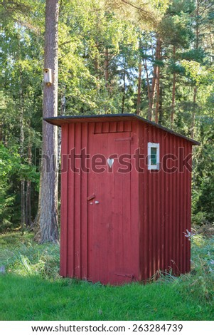Red outhouse in the garden - stock photo