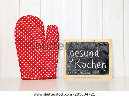 red oven cloth greeting card background - german for healthy cooking - stock photo