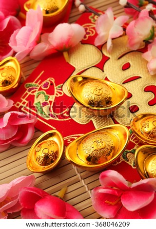 "Red packet , Shoe-shaped gold ingot (Yuan Bao) and both with Chinese character ""Fu"" means fortune on top and Plum Flowers over bamboo mat"