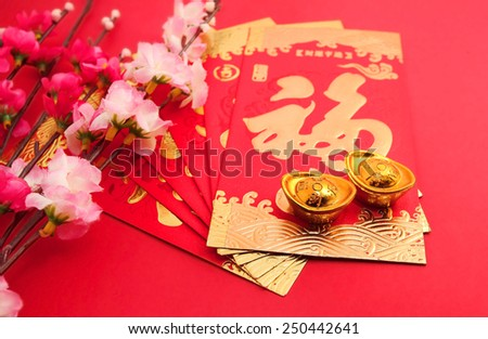 """Red packet (with Chinese character """"fu"""" means fortune) shoe-shaped gold ingot and Plum Flowers on red background with copy space - stock photo"""