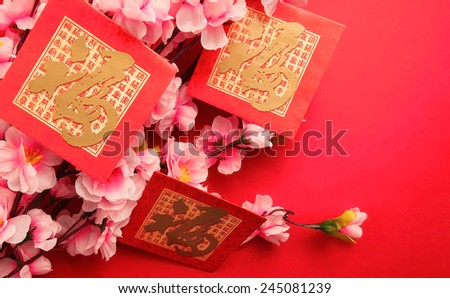 "Red Packets (with the character ""fu"" meaning fortune) with Plum Flowers on red background - stock photo"