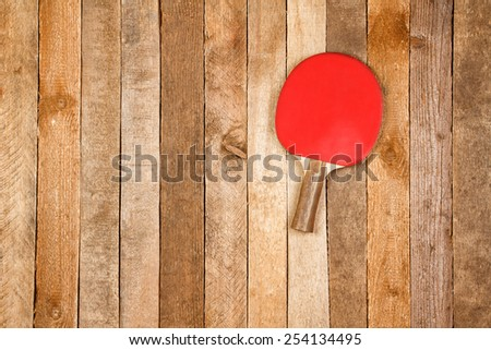 Red paddle for ping pong on wooden background - stock photo