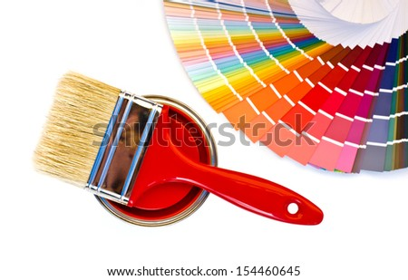 Red paint and swatch. Samples with different shades of red and can of red paint with a brush. - stock photo