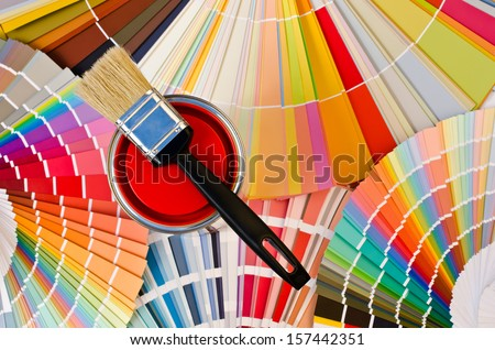 Red paint can. Samples with different shades of red and can of red paint with black brush. Focus on the can, swatches background. - stock photo