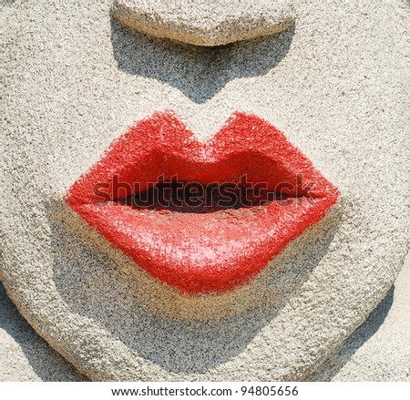 red painted on the stone face lips background - stock photo