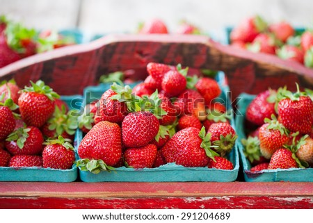 Red painted vintage wooden crate full of fresh organic strawberries