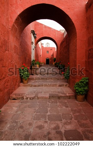 Red painted walls, arches and flying buttresses line an alleyway through the Santa Catalina Monastery in Arequipa, Peru