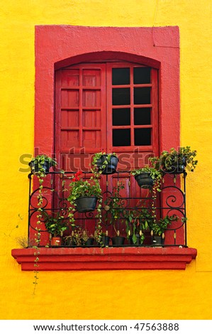 Red painted window with plants and wrought iron railing in Mexico - stock photo