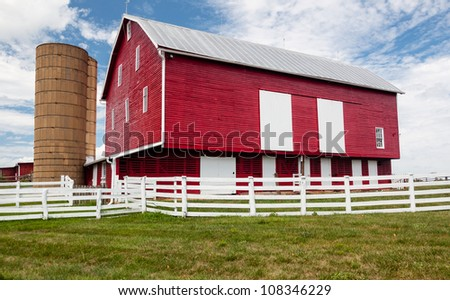 Red painted wooden barn with white door on farm in traditional US style - stock photo