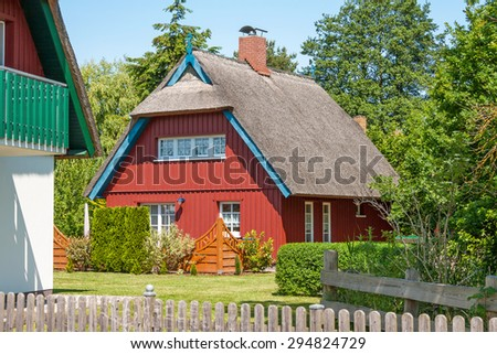 red painted wooden thatched-roof house with garden - stock photo