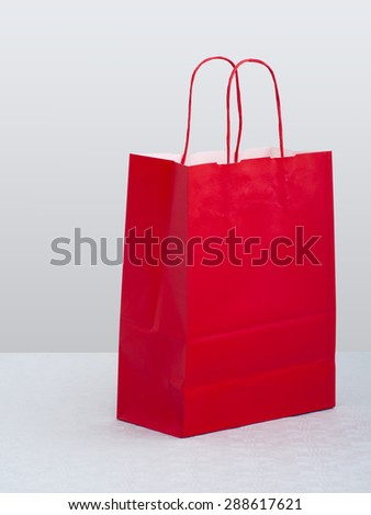Red paper carrier bag, shopper on table.  - stock photo