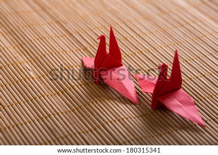 Red paper cranes on bamboo - stock photo