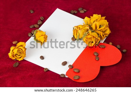 Red paper heart in the envelope with several dried yellow roses and coffee beans - stock photo
