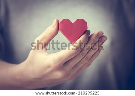 Red paper heart in woman hands. Toned picture - stock photo