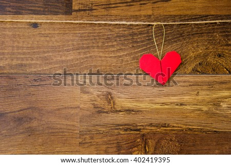 Red paper origami heart hanging on the clothesline on wooden background. Vintage style. Concept image for Christmas holidays. Postcard on wood texture with copy space for text.  - stock photo