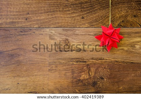 Red paper origami star hanging on the clothesline on wooden background. Vintage style. Concept image for Christmas holidays. Postcard on wood texture with copy space for text.  - stock photo