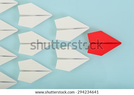 red paper plane leading white ones, leadership concept - stock photo