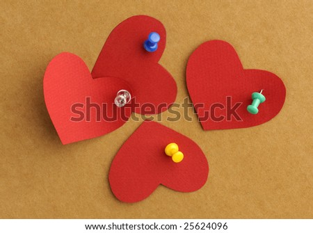 Red paper's hearts with the thumbtacks on the board - stock photo