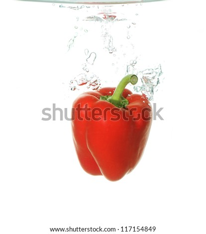 red paprika falling into clear water - stock photo