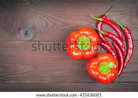 Red paprika with chilli peppers on wooden background - stock photo