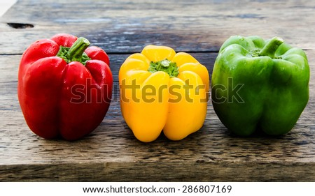 red paprika, yellow paprika   and green paprika on wood background. - stock photo