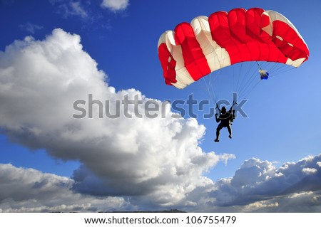 Red parachute landing on stormy sky.