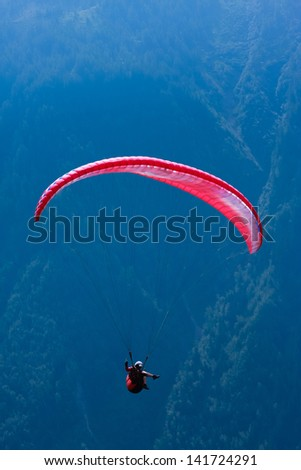 Red paraglide over Alps peaks - stock photo