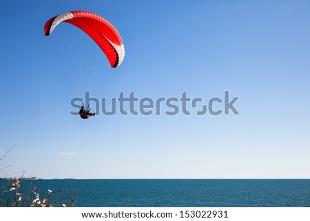 Red paraglider flying in blue sky over the ocean. - stock photo
