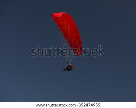 red paraglider on clear blue sky - stock photo