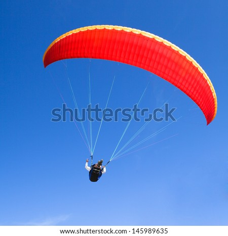red paraglider on the blue sky - stock photo