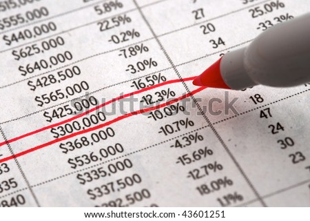 Red pen researching home prices and housing crisis in the newspaper - stock photo