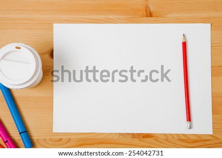 Red pencil, disposable coffee cup and sheet of paper on wooden table. Background for text. - stock photo