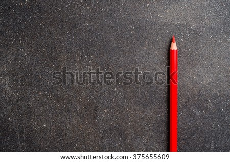 Red pencil on dark table - stock photo