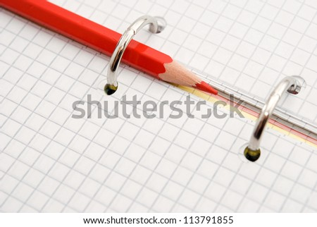 red pencil on notebook background - stock photo