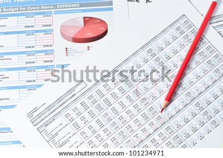 red pencil over financial documents - stock photo