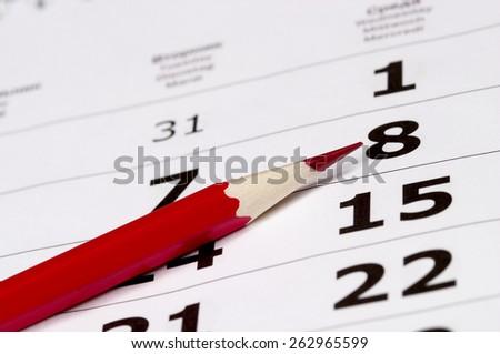 Red pencil over slightly defocused calendar background - stock photo