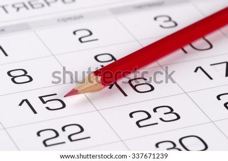 Red pencil over slightly defocused calendar background