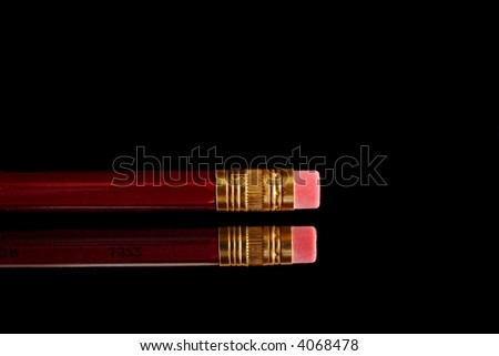 Red pencil with eraser on mirror over black background - stock photo