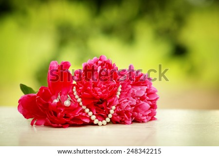Red peonies with necklace and earings - stock photo