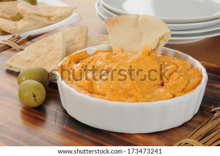 Red pepper hummus with pita bread and green olives