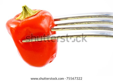 red pepper on a fork on a white background